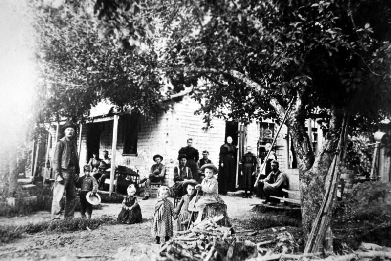 House built by Edmund Richardson in Springville Utah, with Emma Lynette Richardson and John Conover family in front.