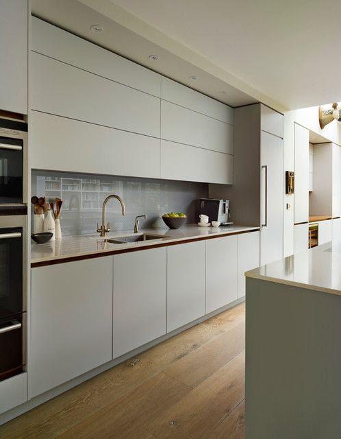 Light grey slab cabinets, reflective backsplash to bounce ...