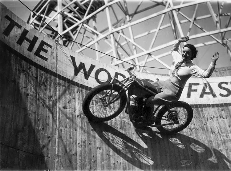"Marjorie Dare (Doris Smith) riding no hands around ""The Wall of Death"" sideshow at the Kursaal amusement park in Essex, England, 1938."