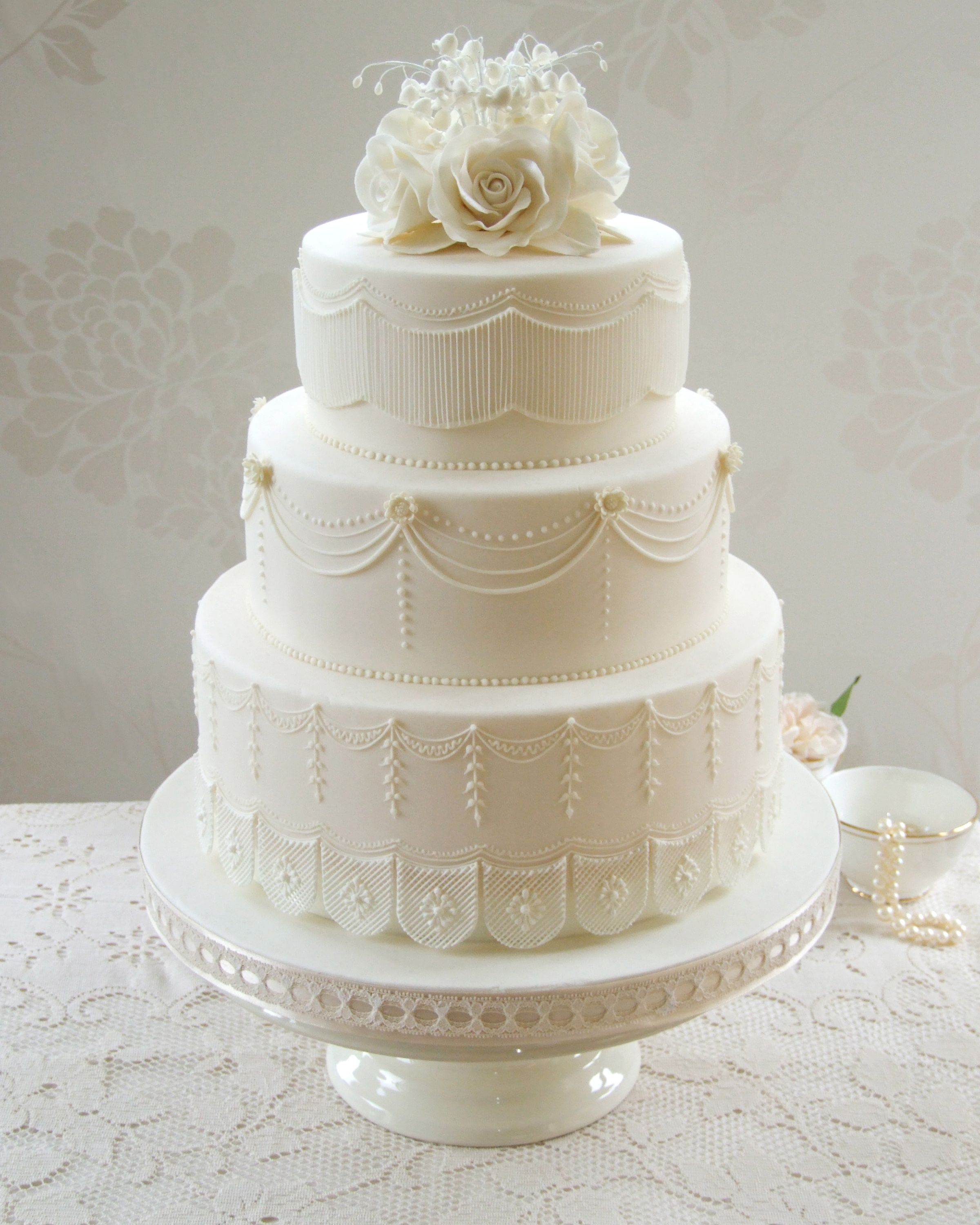 Ivory Wedding Cake Decorated With Piped String Work Swags And Lace