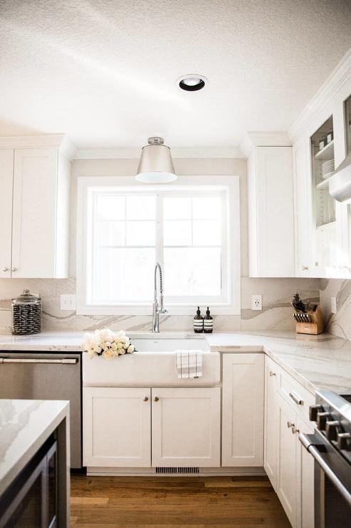 Cambria Brittanica Warm quartz graces a kitchen design on the countertops as well as the backsplash surrounding Sherwin Williams Pure White shaker cabinets. #purewhite
