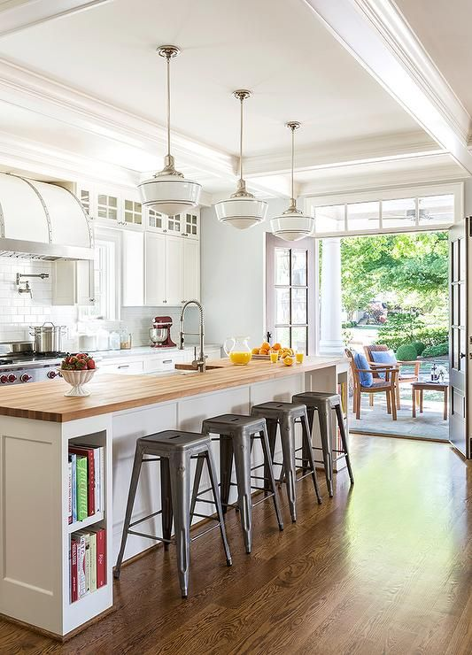 Three Schoolhouse Pendants Illuminate A White Kitchen Island Ed With Cookbook Shelves On Either End Topped