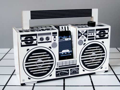 The BerlinBoombox, a cardboard stereo speaker designed and developed by illustrator Axel Pfaender. It is covered with graphic art in bold black and white. You can connect your iPhone (built-in Dock) or any mp3 player.