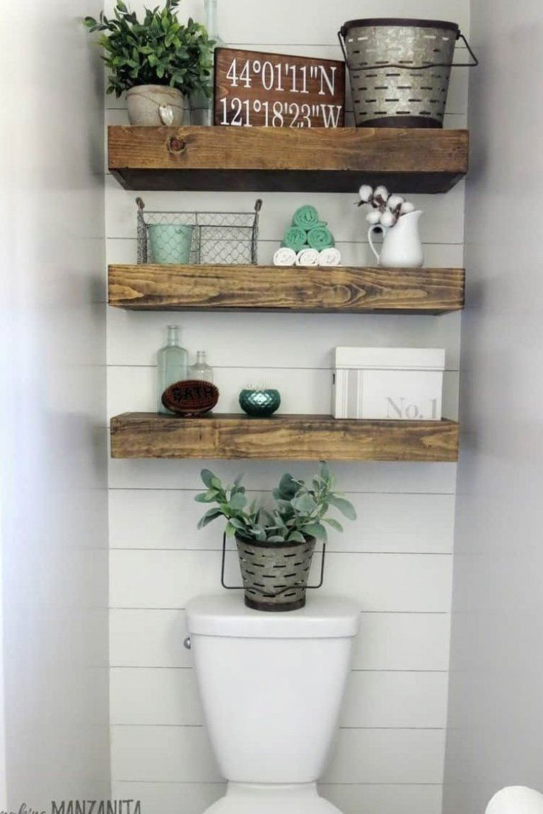 Photo of Farmhouse bathroom with wood floating shelves above toilet with shiplap accent w…