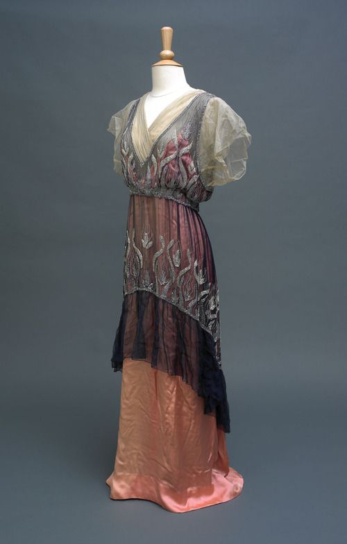 1914. An evening dress of pink silk with blue chiffon over-tunic reaching just below knee level, decorated with sparkling beadware. From the Hull Museums