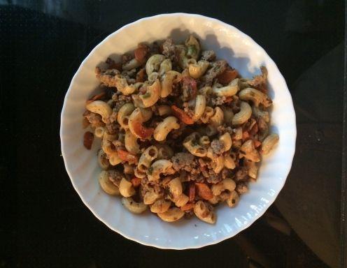 Für die Hascheehörnchen mit Karotten die Hörnchen bissfest kochen. Zwiebel würfeln, in Schmalz leicht anbraten, Faschiertes dazugeben und