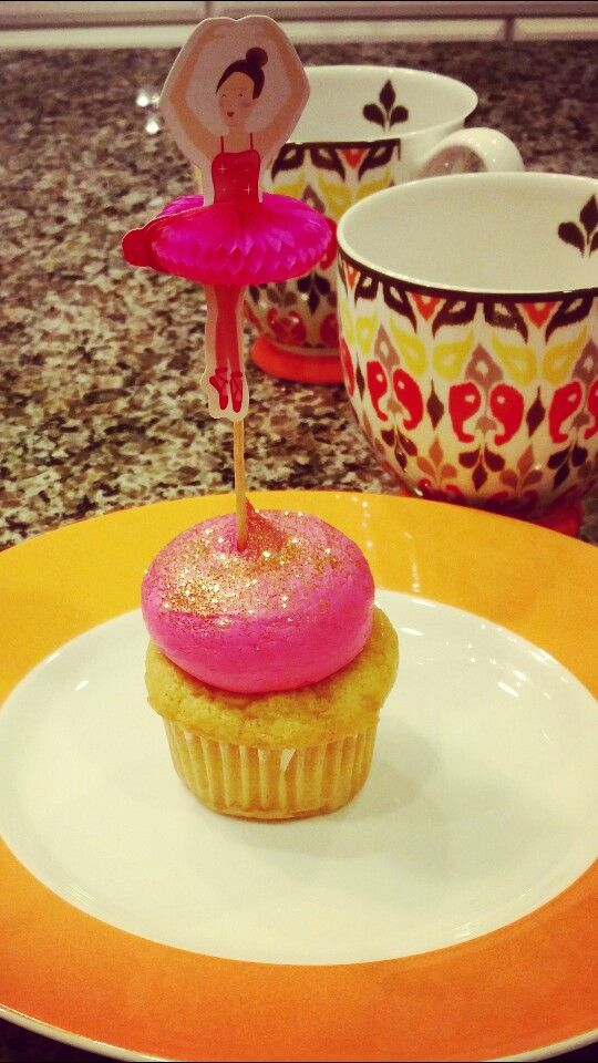 Hot pink cupcake with edible gold glitter on top.