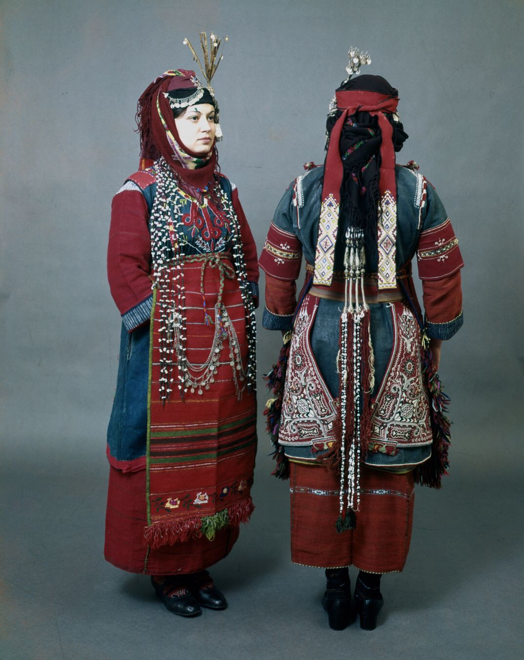 "Front and back Thessaloniki district, Liti and Drymos festive costumes with the characteristic hair ornaments ""bapkes"" and the head ornament ""sourgoutsa"", a metal tassel in the form of a pin. Peloponnesian Folklore Foundation"
