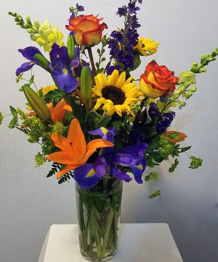 A Beautiful Mixed Floral Arrangement In Yellows Blue Roses Lilies Sunflo Fresh Flowers Arrangements Sunflower Floral Arrangements Fall Floral Arrangements