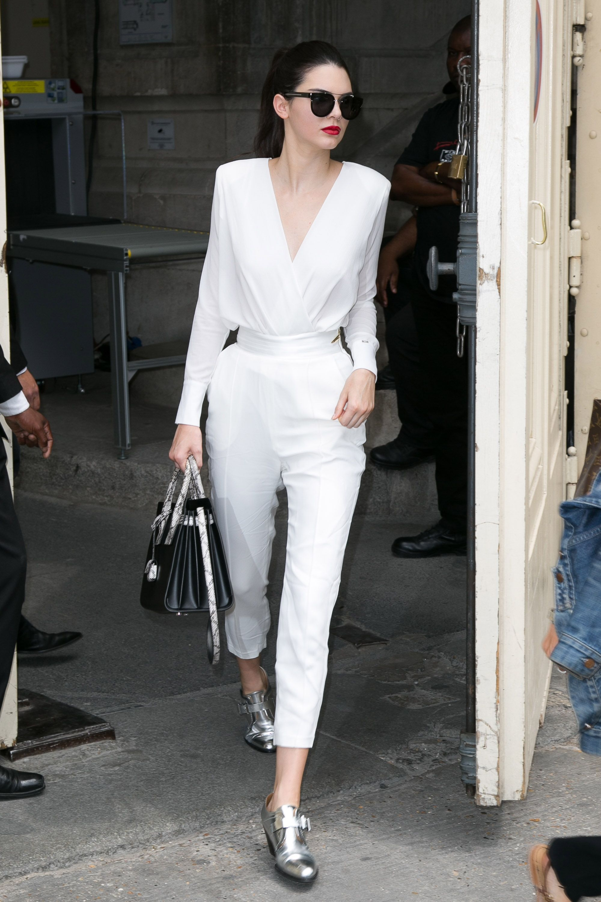 ca1cae60a4f3b4 ... Does Anything But Subtly Hide Her Bralette. Kendall Jenner in Paris  wearing a white blouse and trousers. See more of her best street style  looks here.