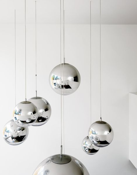 """Bruce worried about what to put in the double-height space above the kitchen table—–until he found these Tom Dixon–designed mirror balls. """"They were installed at random and when William came over that evening, he said, 'Fantastic, well done.' So we left them like that.""""  Photo by: Matthew Williams"""
