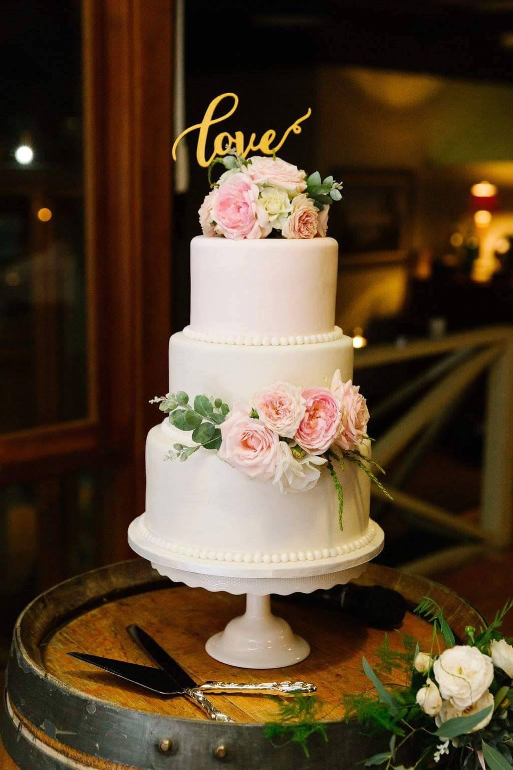 3 tier wedding cake with fresh flowers Bottom tier white