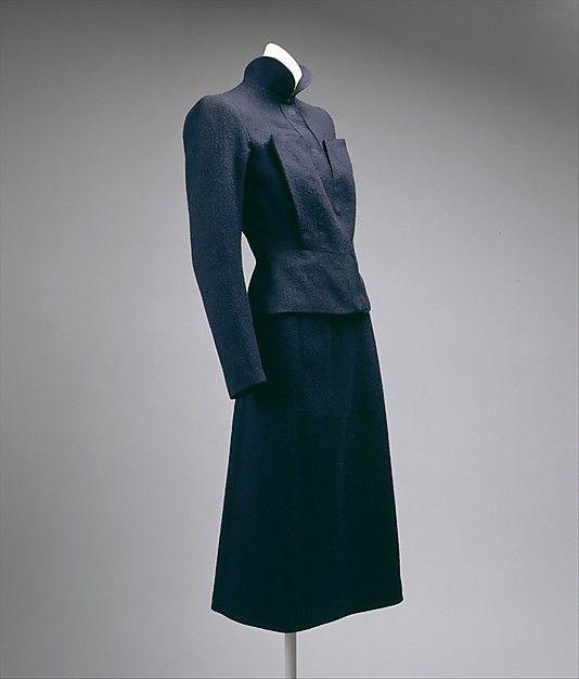 * Elsa Schiaparelli Tailleur en laine bleu marine (fall 1938) 2 poches-poitrine épousent le buste sur toute sa hauteur