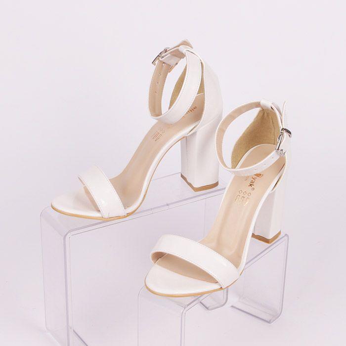 962ca386f64 Изчистени бели сандали от лак, изключително стилни и елегантни. Покрита  пета и каишка с катарама за закопчаване около глезена, с тънка лента над  пръстите за ...