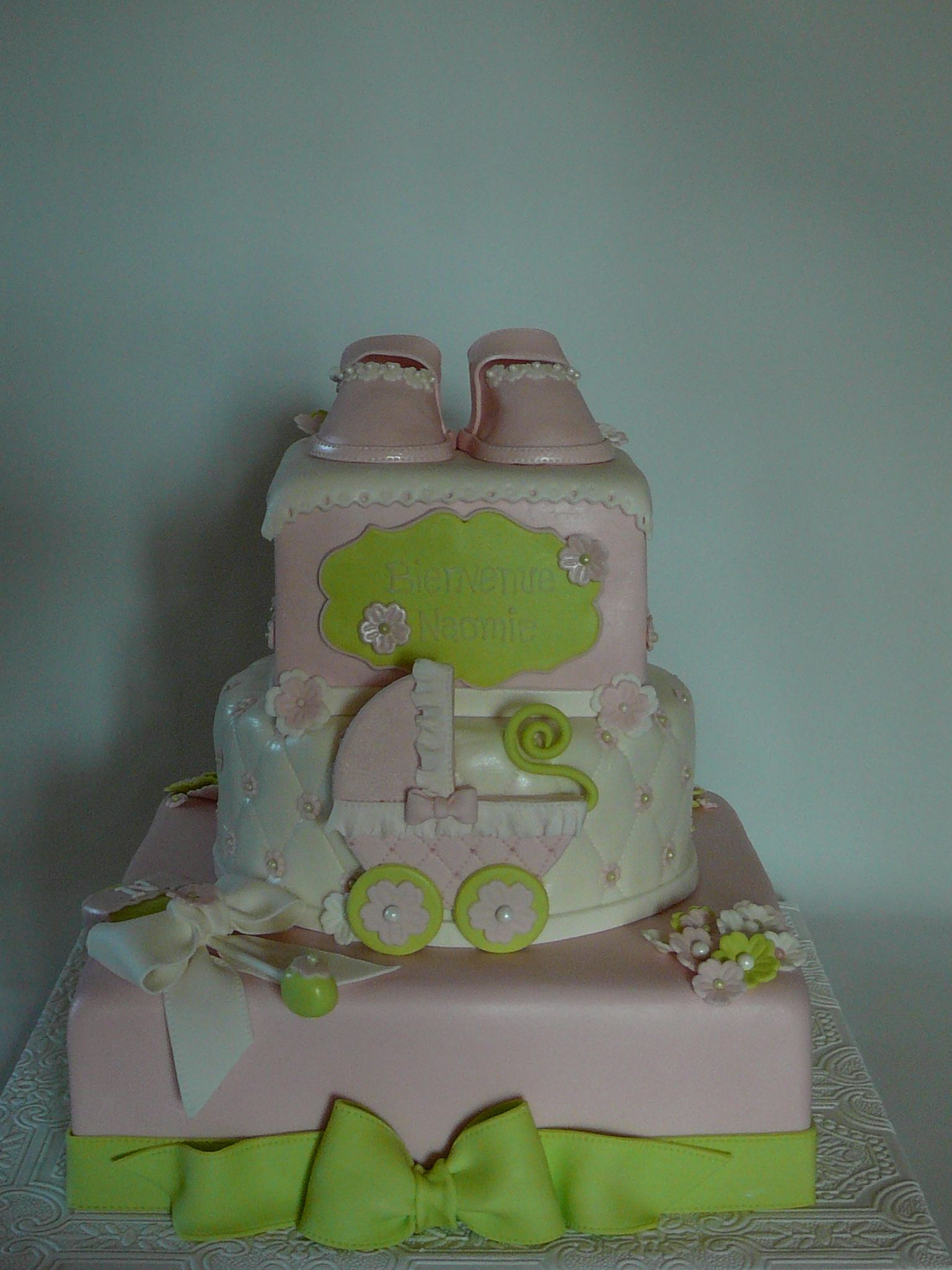Baby carriage and girly shoes christening  - A baby carriage and girly shoes for a baby girl baptism. The baby carriage is hand made with fondant as all the decorations. This is a vanilla cake with buttercream icing covered with fondant.