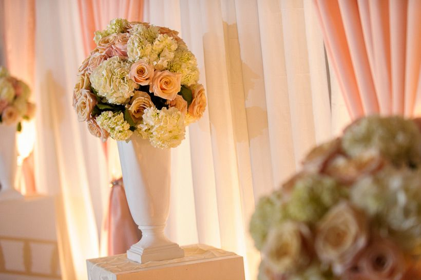 Large hydrangea and rose arrangement in a white urn