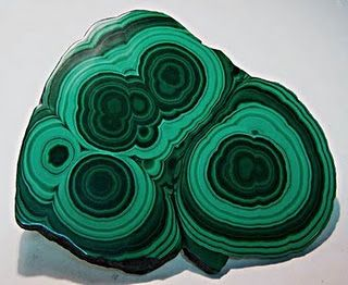 Malachite--It is found in oxidation zones of copper deposits.It is found worldwide and is used as jewelry mainly and smelting into copper