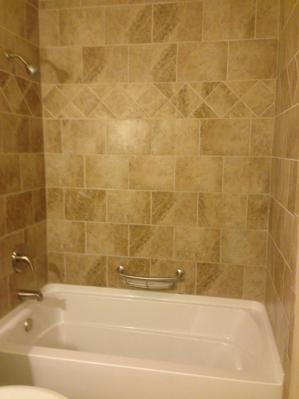 Beige tile tub surround with diamond border pattern. Tiled bathtub ...