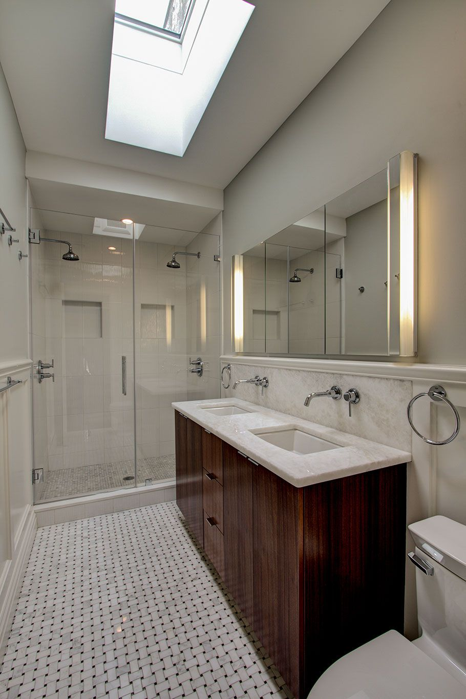 a skylight illuminates this modern brooklyn bathroom and opens up the long narrow space a sleek modern vanity with dual sinks features a dark stained
