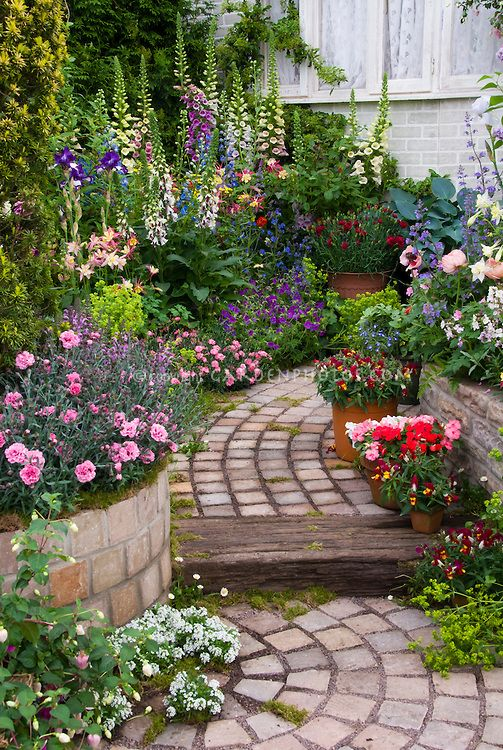 Tiered garden path with raised bed borders of fragrant dianthus digitalis foxglove vertical - Perennial flowers for borders visual gardens ...