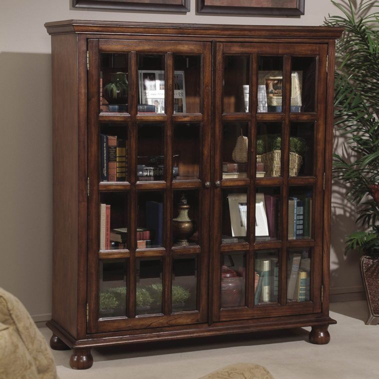 Square Dark Brown Wooden Bookshelves With Glass Doors And Knob Having Curvy Short Base On Grey Rug