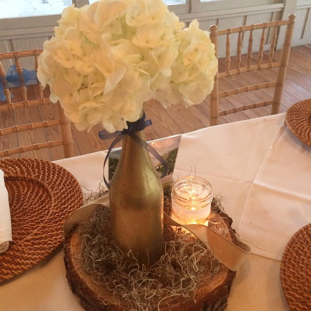 Wedding center pieces. Faux Mercury glass wine bottles, a hydrangea bloom, burlap ribbon, Spanish moss, a photograph and a lace-wrapped Mason jar on wood slices.
