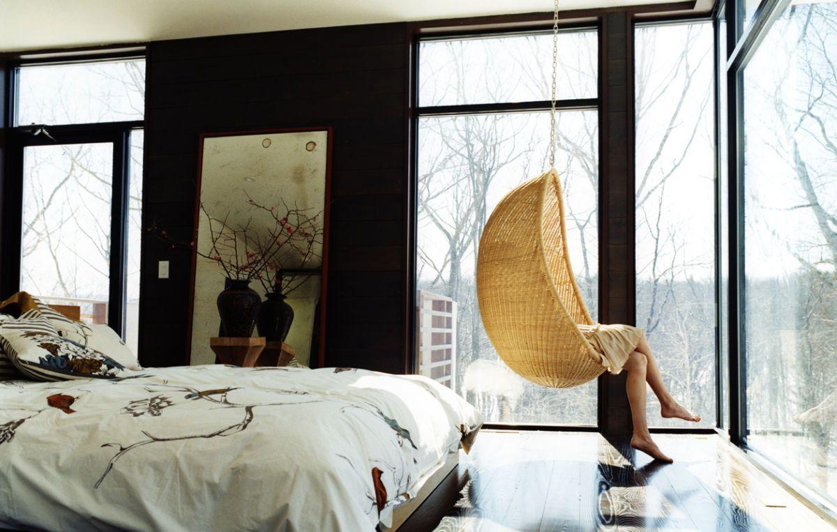 black wall + swing hang chair + big windows