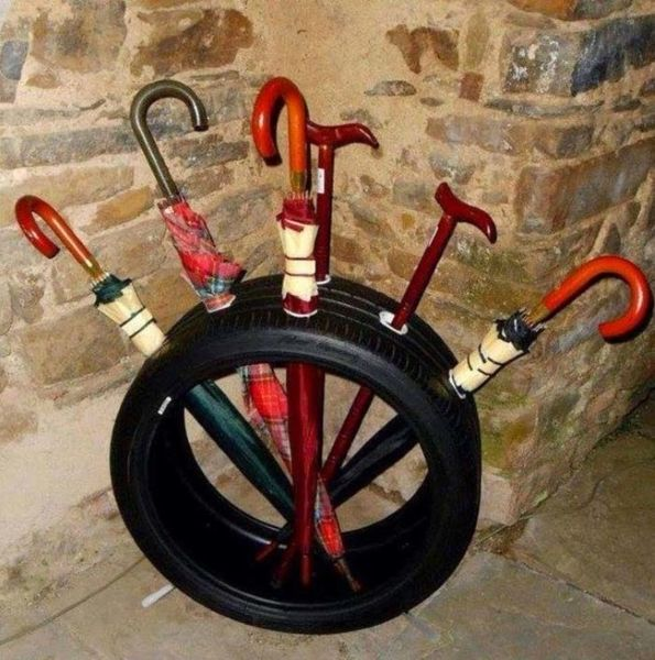 Turn an old tire into an umbrella rack by cutting some holes through it.