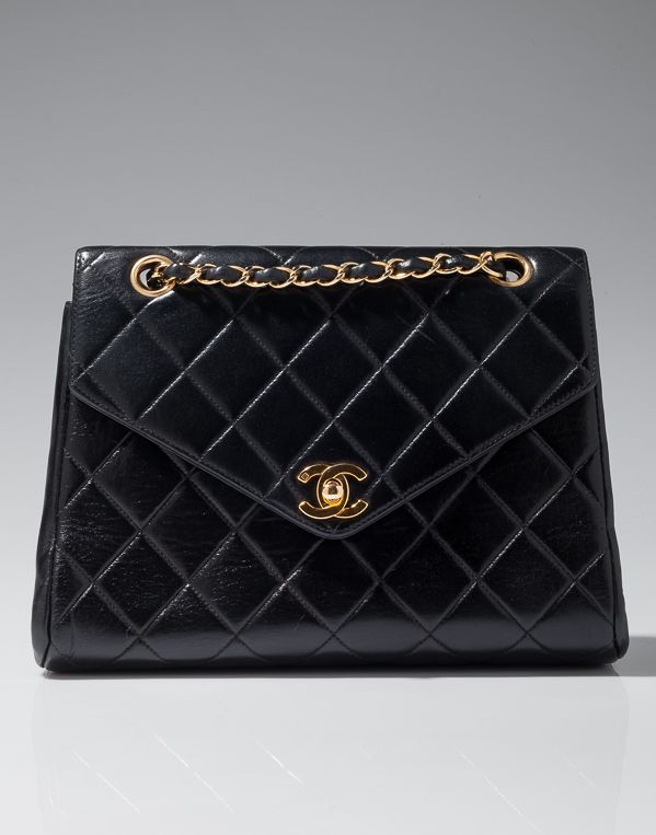 "Black lambskin flap bag with front clasp closure. Rhodium base metal hardware plated gold. Leather interior lining with pockets. Includes duster and cards. 10"" x 3"" x 8"" Back exterior pocket."