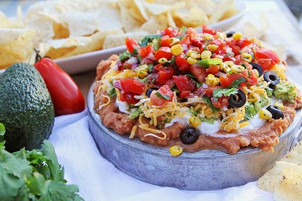 Seriously awesome eight-layer dip! The classic 7-layer dip is kicked up a notch with Roasted Corn!