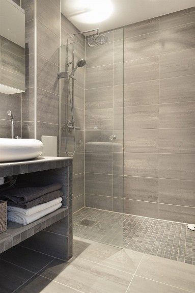Small bathroom that has a curbless shower. Interesting vanity.