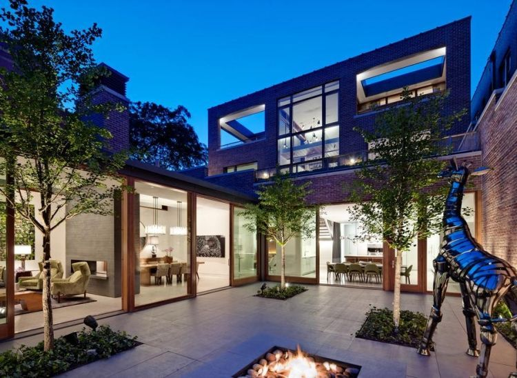 Maison moderne avec sculpture girafe dans la cour intérieure