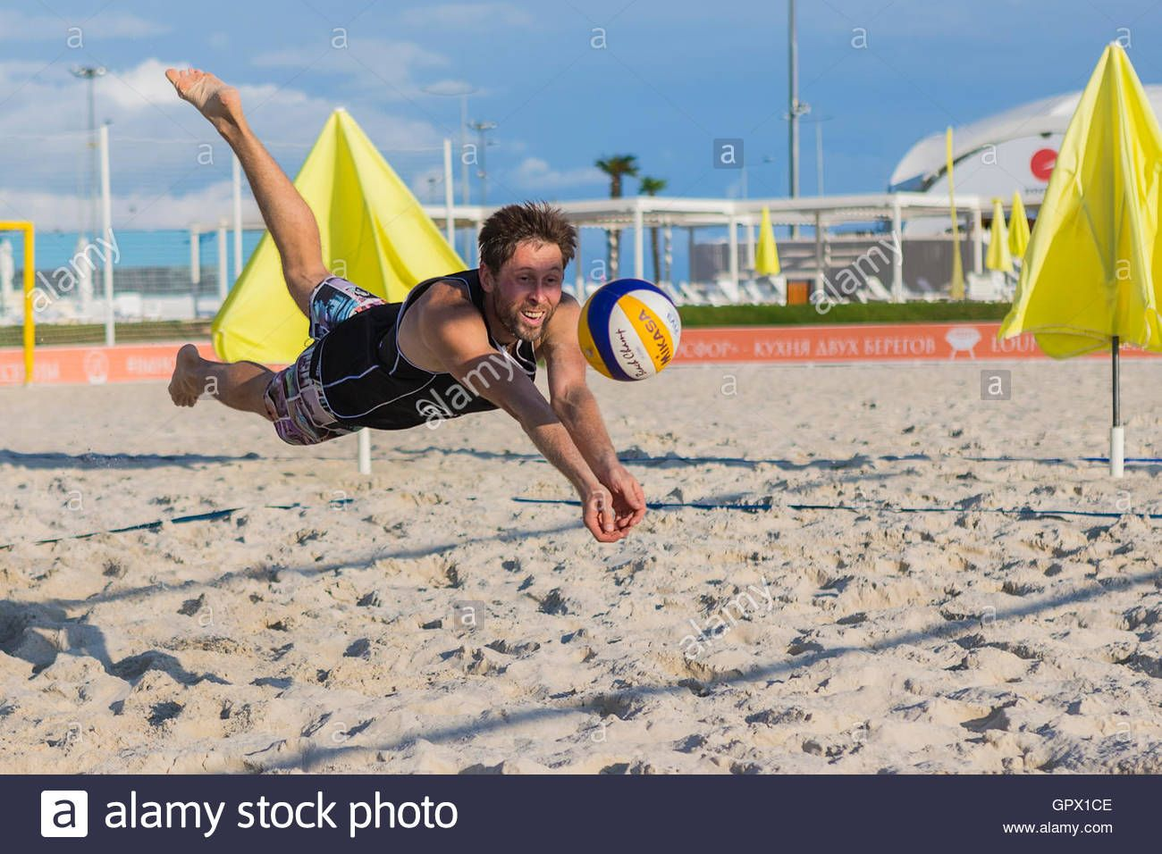 Download This Stock Image Young Man In Motion Plays In Beach Volleyball Beach Volleyball Photo Stock Photos