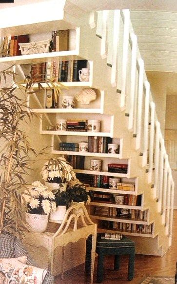 bookcase/shelving behind stairs.