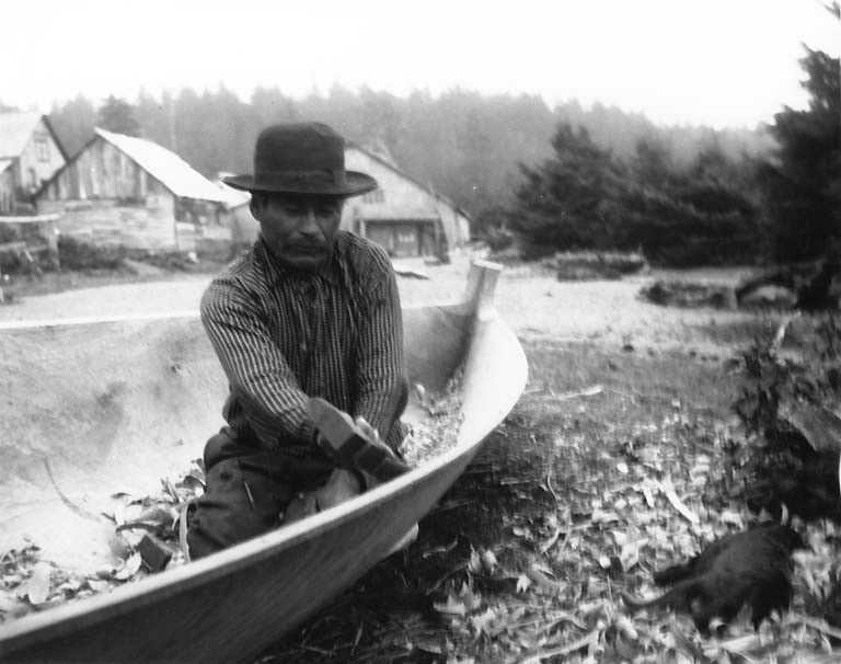 Quileute man named Talicas Eastman making a canoe, Quileute