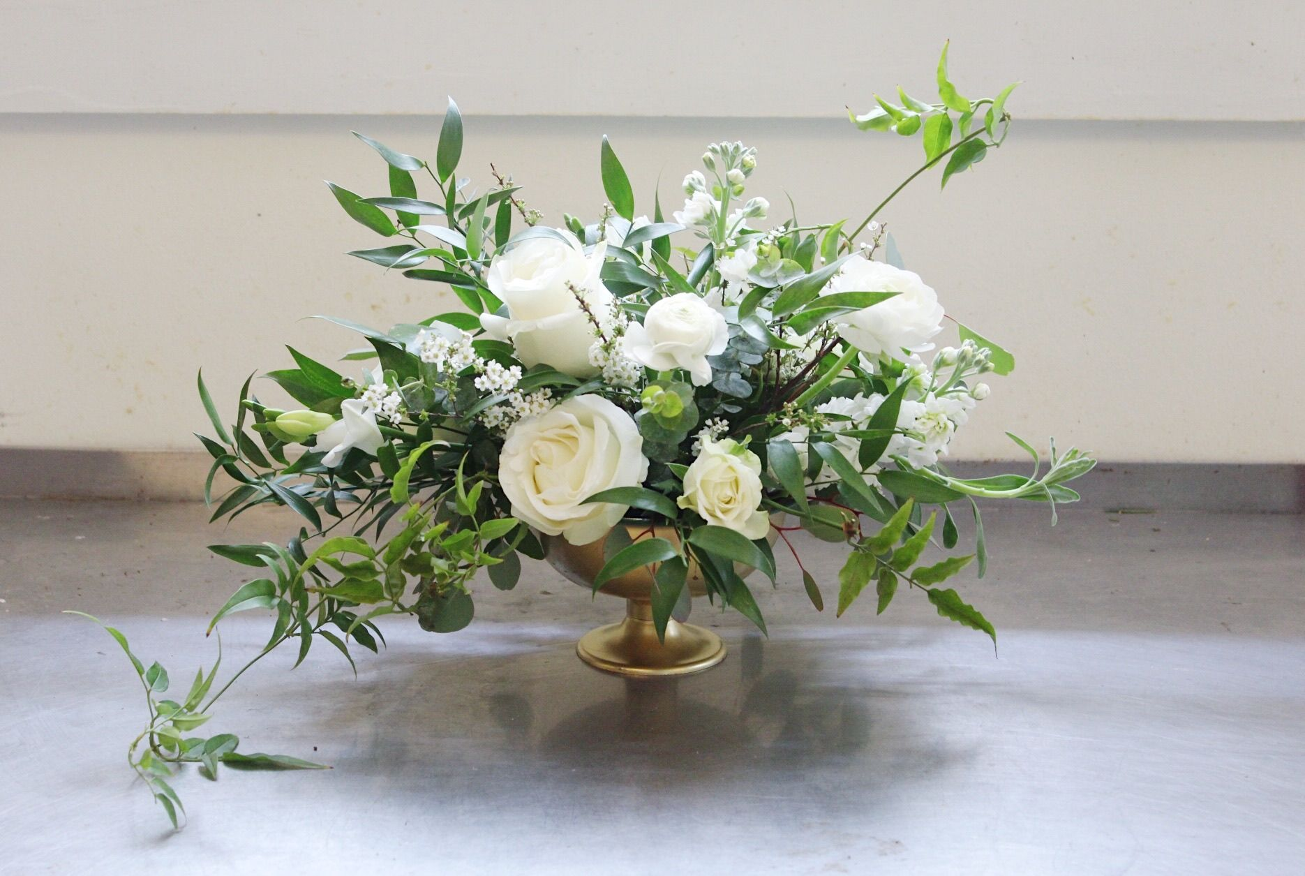 Trailing Greenery With White Roses, Ranunculus, And Stock In A