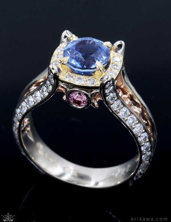 Juicy Vintage Fleur De Lis Engagement Ring! The sides are paved with diamonds. The open shank is inset with repeating fleur de lis symbols. A paved halo surrounds the prong-set center gemstone. It is custom made in the metals and stones you want so start the fun and easy design process today!