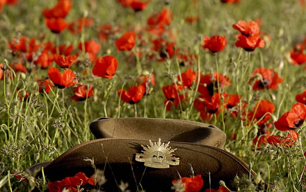 Anzac what it really means to an aussiekiwi lest we forget aussie slouch hat surrounded by poppy flowers in afghanistan mightylinksfo