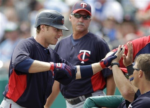 Minnesota Twins' Luke Hughes, left, high-fives teammates after hitting a solo home run in the first inning of a spring training game