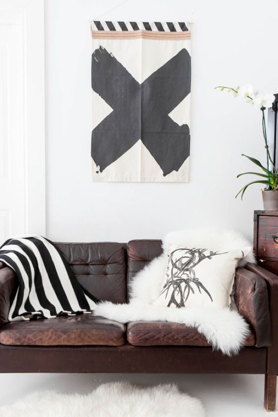 black & white art print, brown leather sofa, sheepskin ...