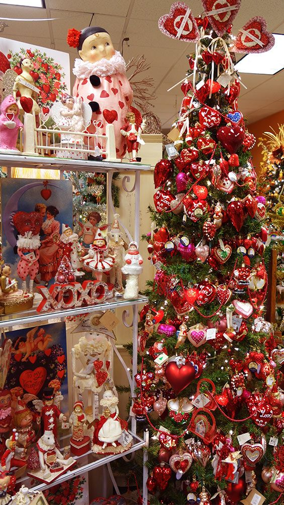 a tree full of heart and valentines ornaments alongside a bakers rack full of vintage valentine figures and decor - Vintage Valentine Decorations