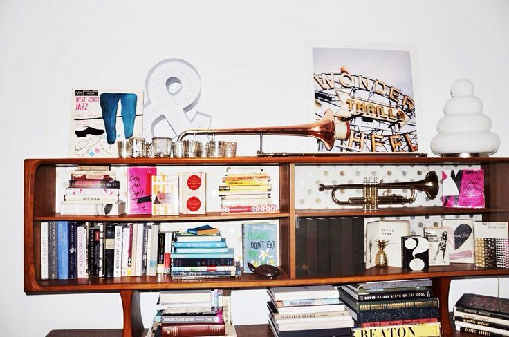 dana's bookcase at home is filled with vintage novels and instruments. (she's been known to play trombone during parties.) (kate spade new york home)