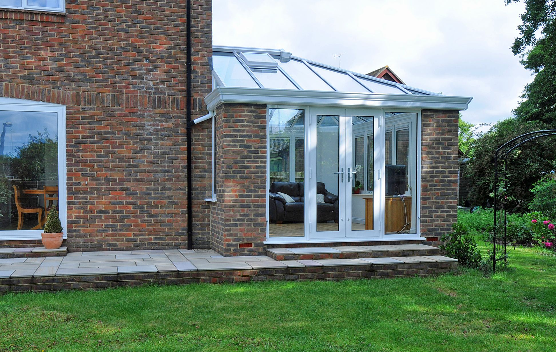 White aluminium garden room with French doors leading out