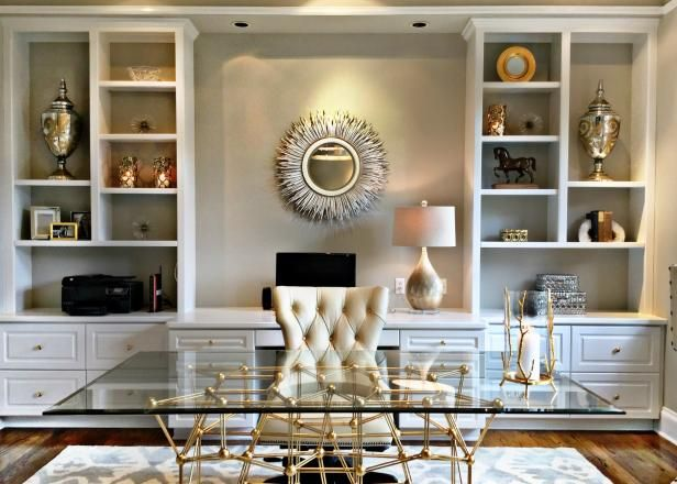 HGTV shares this contemporary, neutral home office with built-in custom bookshelves, carvings and urns as art, starburst mirror, recessed lighting, metallic table lamp, tufted cream-colored office chair, brass-and-glass desk, area rug and hardwood floors.