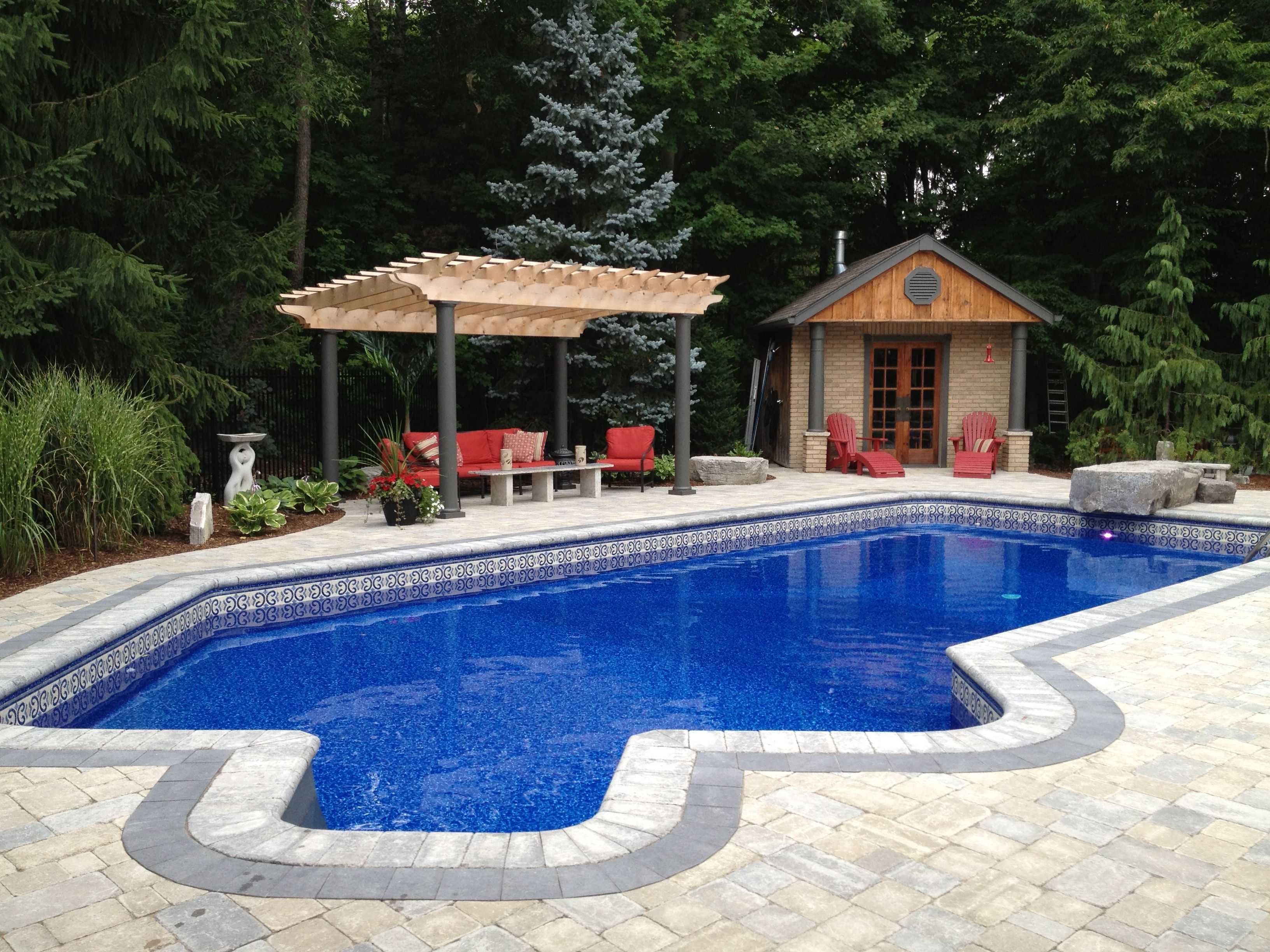 a stunning view across the pool to the custom cedar pergola and
