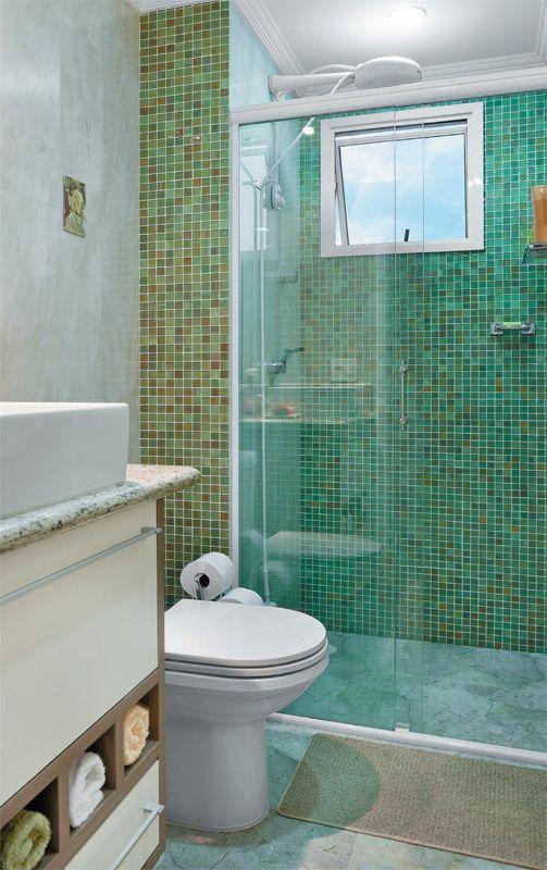 Pastilhas de vidro, no boxe e na faixa ao lado do vaso sanitário; demais superfícies, porcelanato imitação de mármore; gabinete planejado, com gavetas e nichos para toalhas.