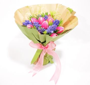 This one's real special because we pushed the flowers deeper into an apple-green paper cone. But the 10 pink tulips still stand out in a bed of purple and green accompaniments. Tied with a pretty organza ribbon.