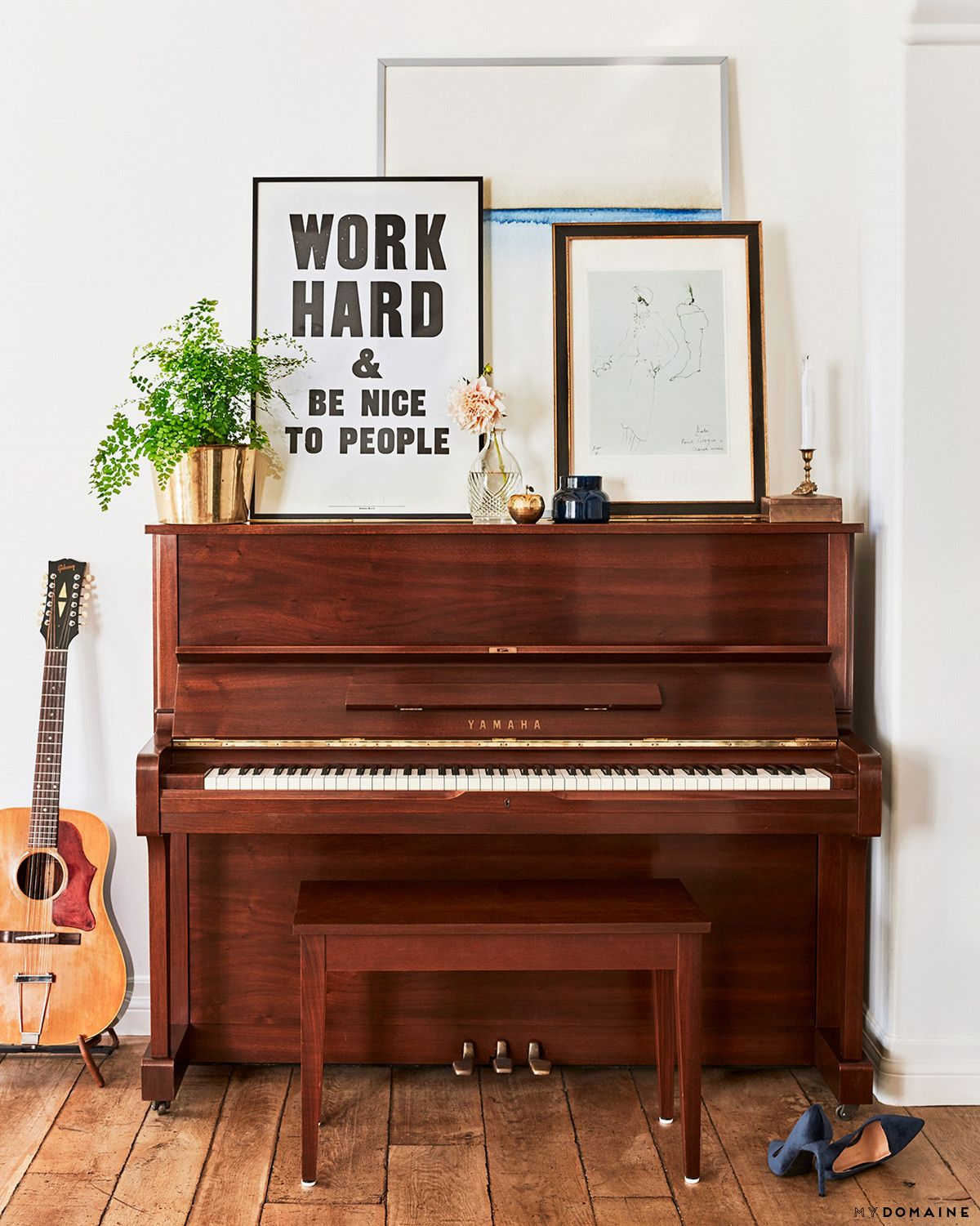 Lauren Conrad's living space with a vintage piano with art propped above and an indoor plant