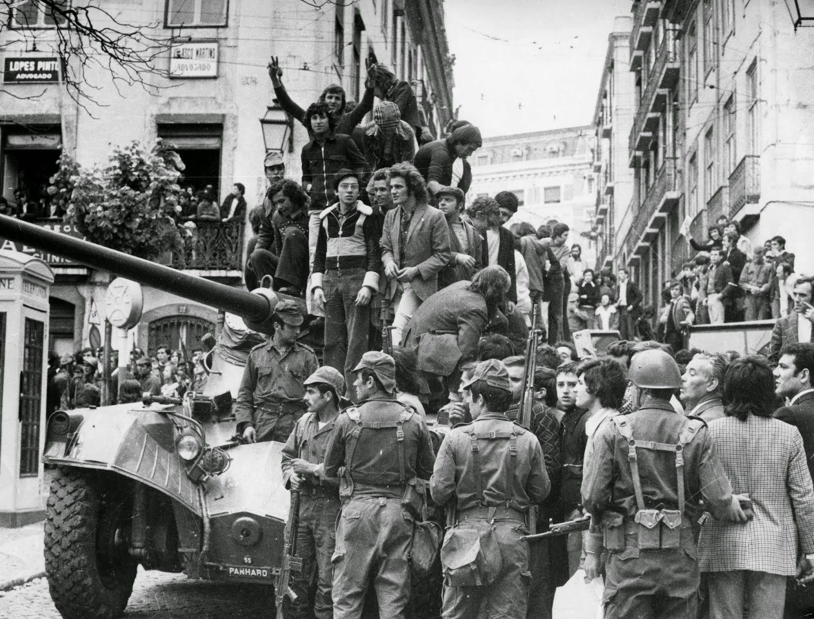 """1974 Carnation Revolution - Citizens of Lisbon join in with the Portuguese Army soldiers of the Armed Forces Movement (Movimento das Forças Armadas) as they overthrow the Fascist """"Estado Novo"""" regime."""