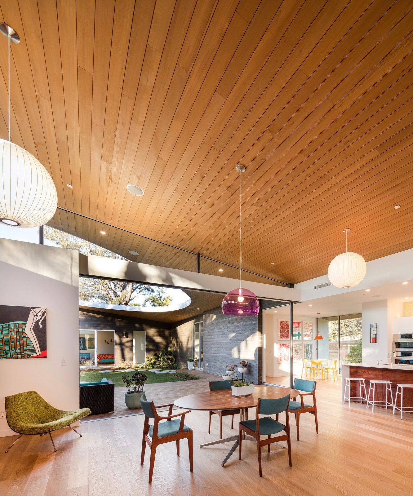 A large glassless opening on the sloping curved shed roof of this californian home opens the courtyard to the sky and the elements while give the